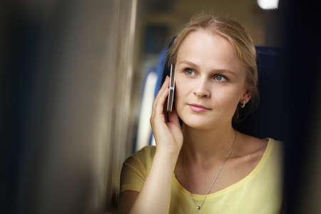 Attractive young woman with a serious attentive expression listening to a conversation on her mobile phone or waiting for a connection, while travelling by train, close up head and shoulders photo