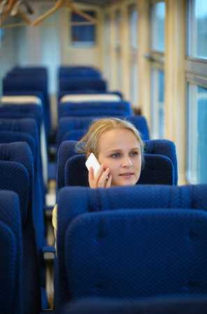 emigrant: Woman sitting in an empty tram or passenger train talking on her mobile phone as she waits for her transportation to depart Stock Photo