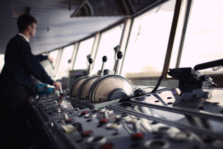 navegacion: Oficial de navegaci�n conducir el barco en el r�o. Foto de archivo