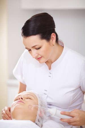 pulizia viso: Donna ed estetista durante la procedura spa viso nel salone di trattamento di bellezza