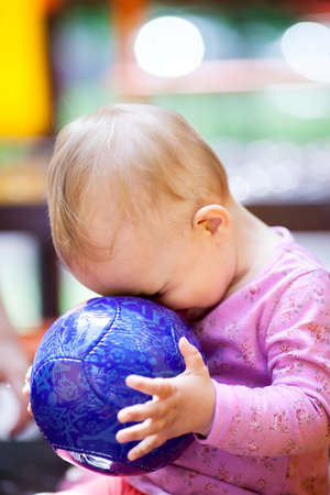 Cute little baby playing with a big blue ball sitting with its face pressed up against the ball, side view photo