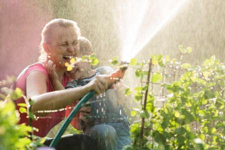 jet stream: Riendo madre e hijo jugando con un aspersor en el jardín dirigir el spray en el aire para que caiga de nuevo mojarlas