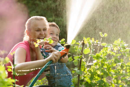 Young mother and cute son playing with water hose in the garden