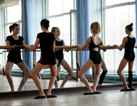 barre: Three ballet dancers warming up before practice starts
