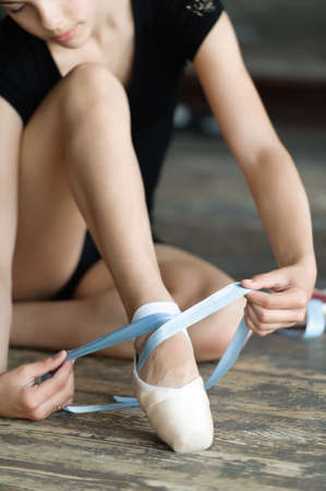ballet clásico: Muchacha con las piernas largas que ata sus zapatos de ballet en el suelo Foto de archivo