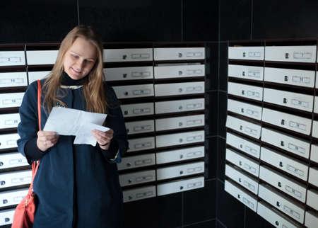 buzon: Lectura de la mujer feliz recibió la carta de pie entre los buzones de correo Foto de archivo