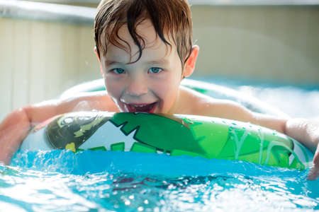 flotation: Cute boy in inflatable ring having fun in the swimming pool Stock Photo