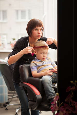 he she: Little boy getting a haircut from hairdresser  She combing his hair while he playing with toy