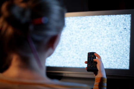 tv set: Back view of woman with remote control in front of TV set with noise on the screen Stock Photo