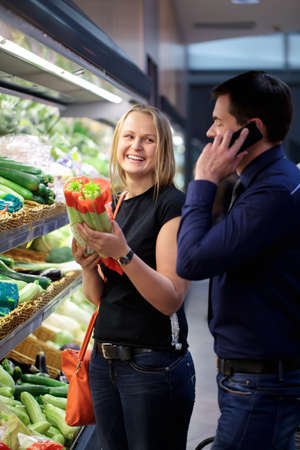 Woman in produce section of a supermarket holding vegetables smiling looking at man on the phone beside her photo