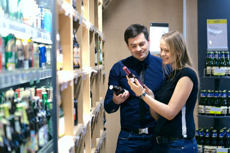 Attractive couple standing choosing wine in a bottle store looking at two bottles off the shelves full of merchandise Stock Photo