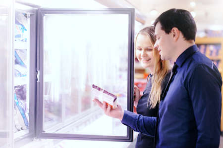 Couple in the frozen goods section of a grocery store picking out food from the freezer photo