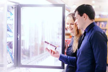 alimentos congelados: Pareja en la sección de productos congelados de un supermercado escogiendo los alimentos del congelador