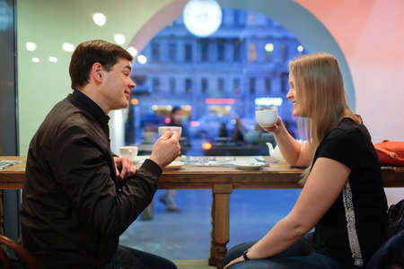 teatime: Man and woman chatting over a cup of coffee inside a cafe or restaurant