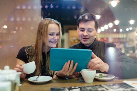 Happy young man and woman drinking coffee while looking on tablet photo