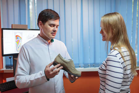orthopaedist: Woman consulting foot doctor in his clinic