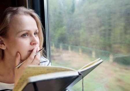 journal intime: Jeune femme sur un �criture de train notes dans un journal ou une revue regarder pensivement par la fen�tre avec son stylo sur ses l�vres qu'elle pense de ce qu'il faut �crire