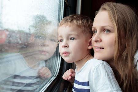 母と息子は日を楽しむ列車の窓を通して見るガラスに映る小さい男の子の顔と旅行します。