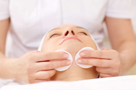 cosmetician: Close-up shot of a womans face being cleaned with cotton discs by a cosmetician Stock Photo