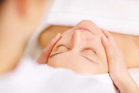 Close-up shot of a woman during the seance of facial massage in beauty spa