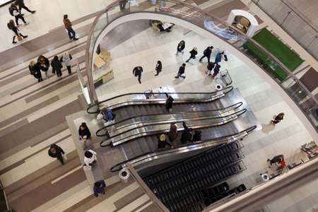 high angle shot: High angle shot of people walking around and riding escalator in modern trade centre Editorial