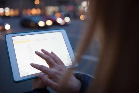 Vrouw wat betreft de tablet scherm lopen in de straat 's nachts Stockfoto