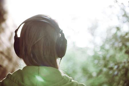 밝은 햇빛 인스 타 그램 스타일의 컬러 톤에게 대한 음악 야외 듣고 헤드폰에서 여자의 빈티지 사진 스톡 콘텐츠
