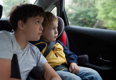 Two boys in the car looking out the window  Little boy sitting in the child safety seat