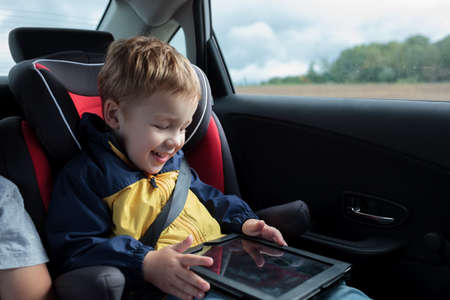 child seat: Happy little boy in the car sitting in child safety seat and playing with tablet PC