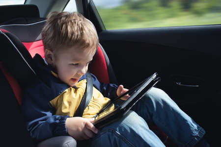 Excited little boy in the car playing with touchpad sitting in child safety seat photo