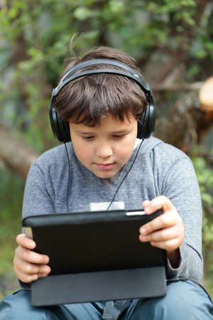 Teenager boy in headphones using tablet PC  He listening to music or watching movie photo