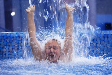 Excited woman with her hands up enjoying strong shower in the swimming pool photo