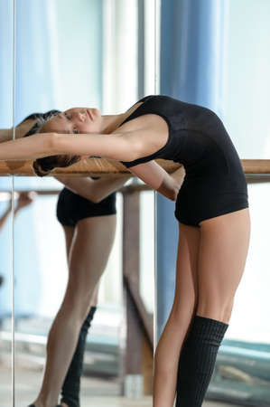 barre: Young graceful ballet dancer stretching out at the barre in the studio