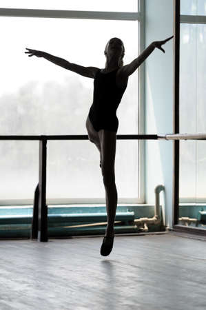 barre: Silhouette of a ballerina making arabesque in the air  Shot against the window with sunlight Stock Photo