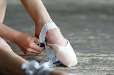 근접 한 스튜디오에서 바닥에 앉아 발레 신발을 벗고 발레리나의 총