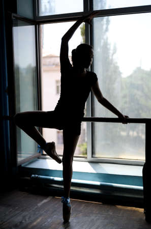 barre: Black silhouette of a ballet dancer in position at the barre near the window