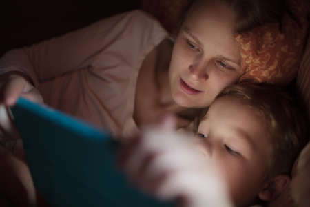 woman tablet: Mother and little son watching video or playing on touchpad lying in bed at night