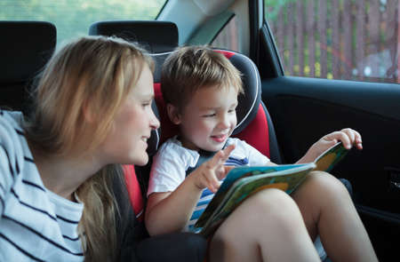 Mother and little son in the car  Woman watching boy looking through the book  Kid sitting in child safety seat