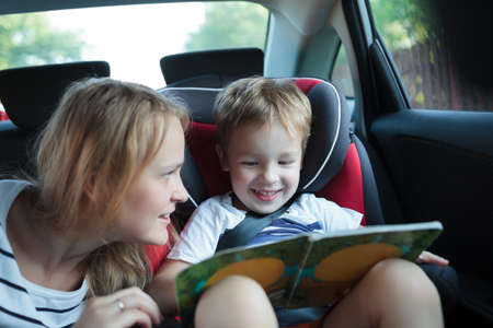 Little boy in a car sitting in child safety seat looking at the pictures in the book, mother watching him