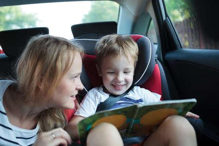 작은 책에있는 사진을보고 어린이 안전 좌석에 앉아 차 소년, 어머니 그를보고 스톡 콘텐츠