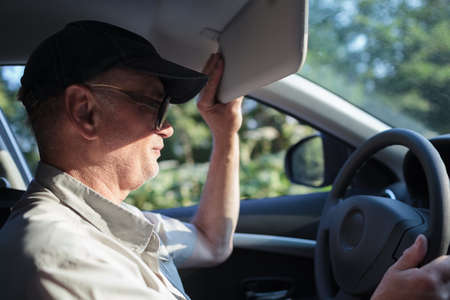 바퀴에서 노인의 측면보기는 선 바이저와 태양으로부터 자신을 숨기려고