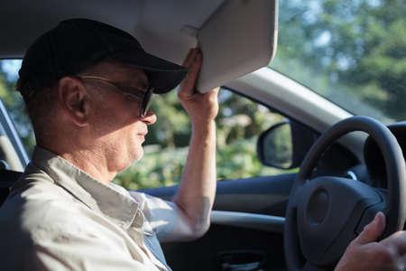 luz solar: Vista lateral de um homem velho ao volante tentando esconder-se do sol com uma viseira de sol