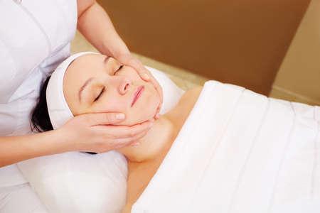 Close-up shot of a woman getting facial massage at beauty treatment salon