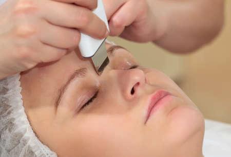 pulizia viso: Close-up shot di una donna alla stazione termale di bellezza ottenere un trattamento viso con pulizia del viso ad ultrasuoni