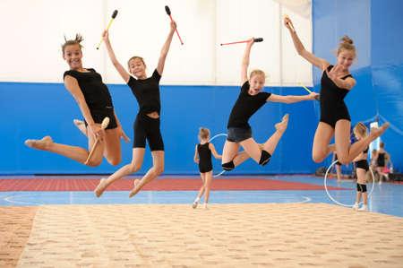 gymnastique: Groupe de quatre jeunes gymnastes féminines posant avec clubs indiens dans un saut en hauteur Banque d'images