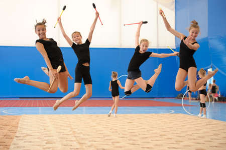 Group of four young female gymnasts posing with Indian clubs in a high jump