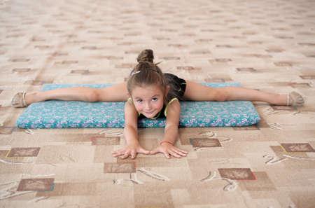 Little girl doing leg-split on the floor. Gymnastics for young females