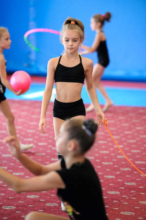Girls exercising with ball and hula hoop during gymnastics class. Focus on the girl holding rope photo