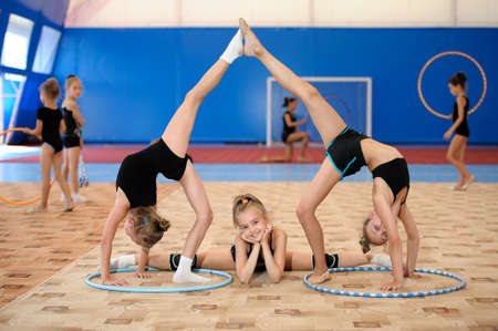Young female gymnasts posing. Girl doing leg-split between two ones stretching legs up