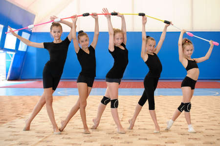 Five young female gymnasts standing by age and making bow with Indian clubs